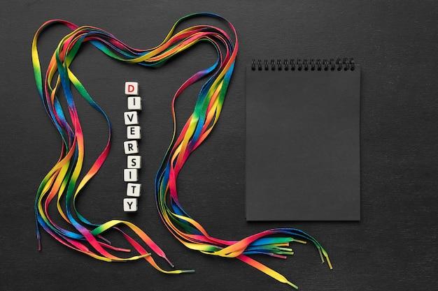 Arrangement De Lacets Colorés Sur Fond Sombre Avec Bloc-notes Noir Photo gratuit
