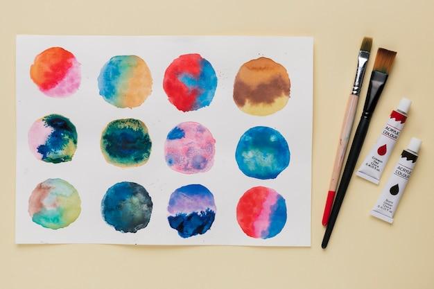 Arrangement de peinture abstraite en cercle; pinceau et tube de peinture Photo gratuit