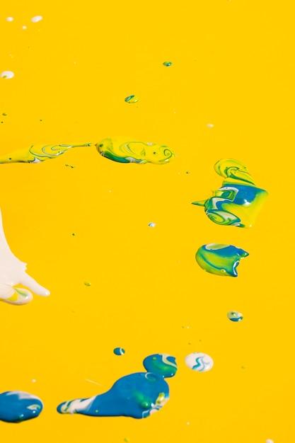 Arrangement avec de la peinture bleue sur fond jaune Photo gratuit
