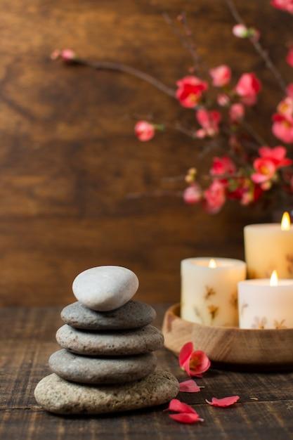 Arrangement avec des pierres de spa et des bougies allumées Photo gratuit