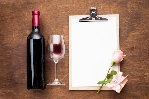 Arrangement plat avec du vin et du presse-papiers Photo gratuit