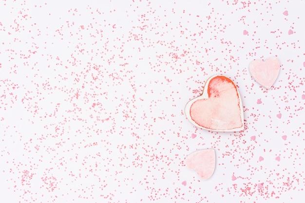 Arrangement plat avec fond en forme de coeur rose et rose Photo gratuit
