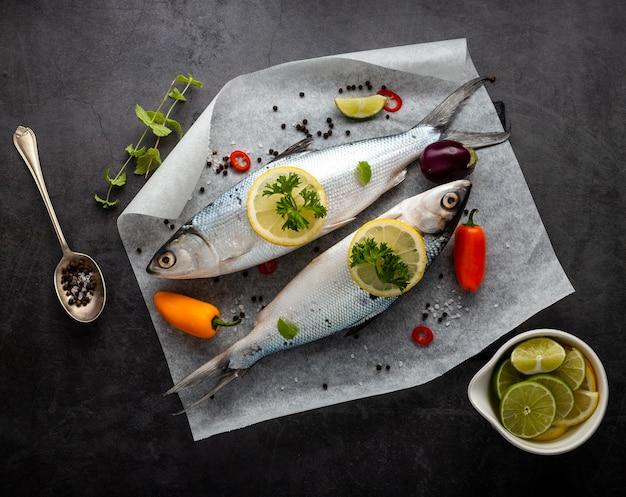 Arrangement plat laïque avec des poissons et fond de stuc Photo gratuit