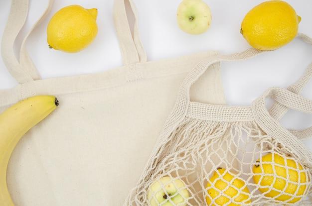 Arrangement à plat avec sac à fruits et coton Photo gratuit