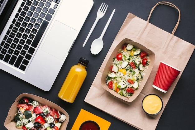 Arrangement plat avec salade et ordinateur portable Photo gratuit