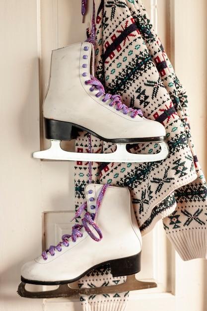 Arrangement avec pull et patins à glace suspendus Photo gratuit