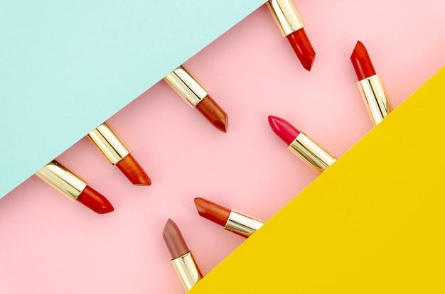 Arrangement de rouges à lèvres colorés sur fond coloré Photo gratuit