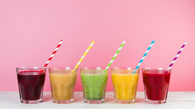 Arrangement de smoothies avec un fond rose Photo gratuit