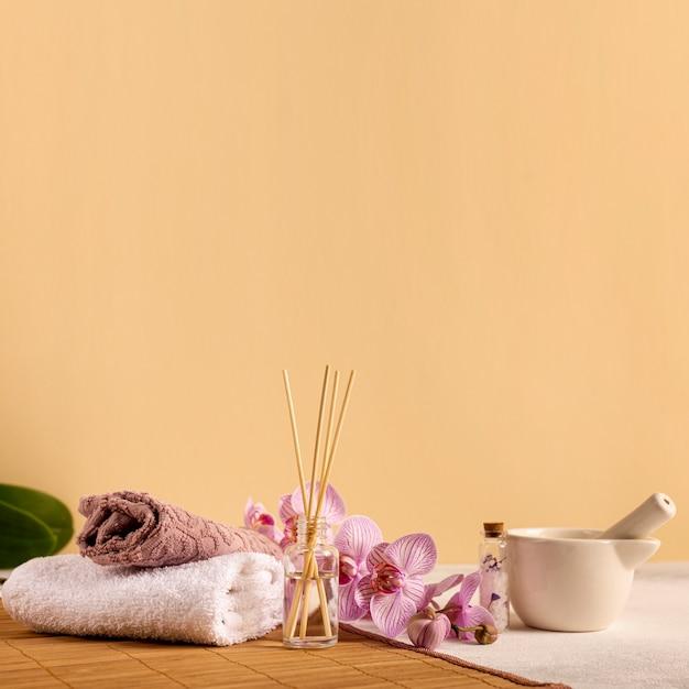 Arrangement spa avec des serviettes et des fleurs Photo gratuit
