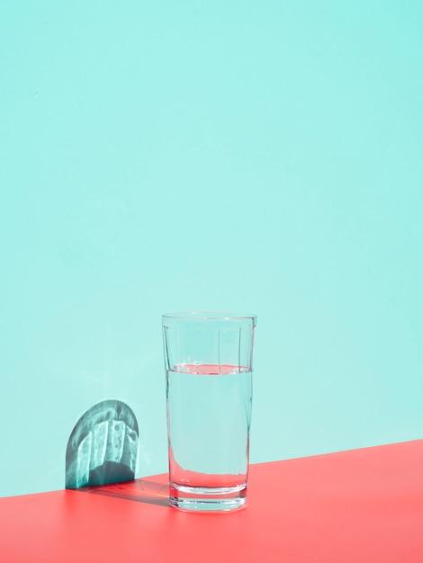 Arrangement avec un verre d'eau près du mur bleu Photo gratuit