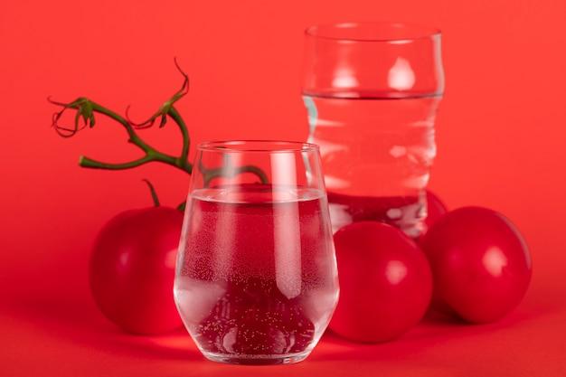 Arrangement de verres à eau et tomates Photo gratuit