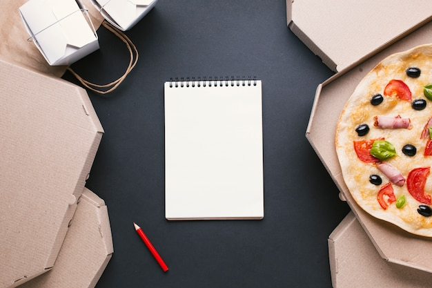 Arrangement de vue de dessus avec boîtes à pizza et cahier Photo gratuit