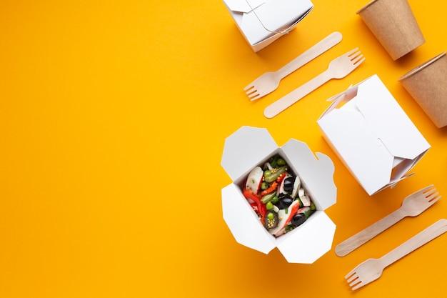 Arrangement vue de dessus avec des boîtes de salade et de la vaisselle Photo gratuit