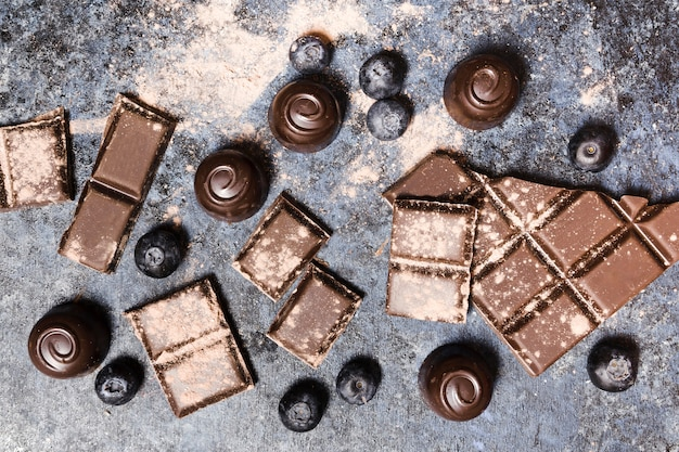 Arrangement De La Vue De Dessus Avec Des Bonbons Au Chocolat Et Des Bleuets Photo gratuit