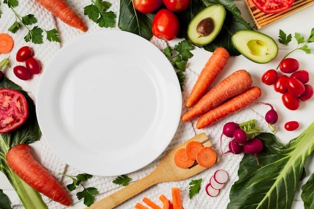 Arrangement de vue de dessus avec légumes et assiette vide Photo gratuit