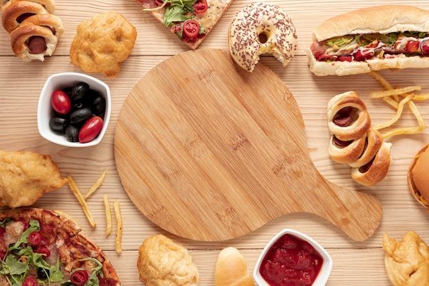 Arrangement de vue de dessus avec de la nourriture et une planche à découper Photo gratuit