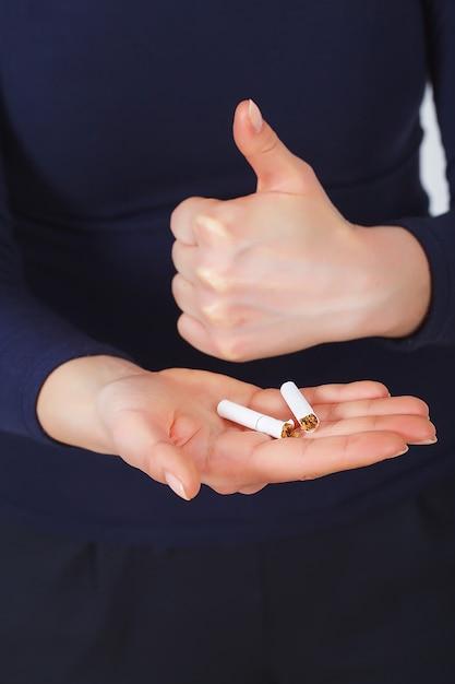 Arrêter De Fumer. Belle Femme Cassant La Cigarette En Deux Photo Premium