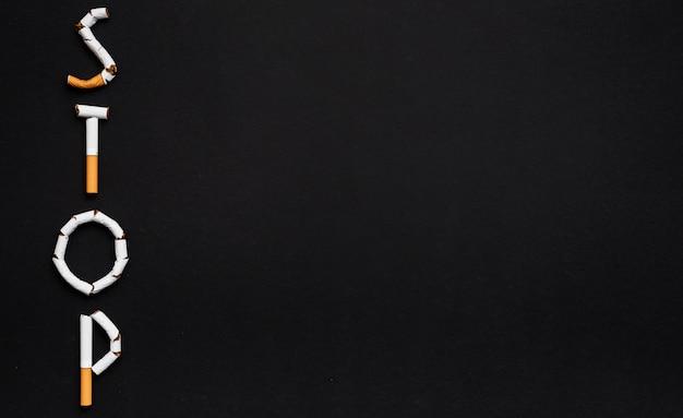 Arrêtez le texte arrangé avec cigarette sur fond noir Photo gratuit