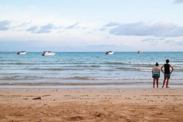 L'arrière d'un couple debout sur la plage et regardant vers la mer avec des bateaux rapides. Photo Premium