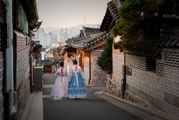 L'arrière de deux femmes portant un hanbok marchant dans le village de bukchon hanok à séoul, en corée du sud. Photo Premium