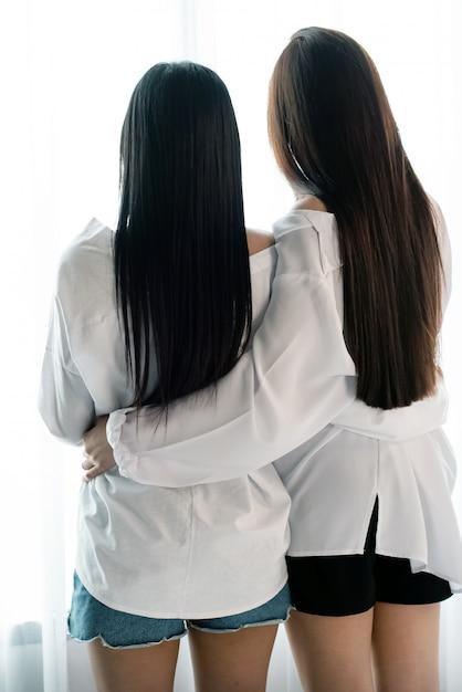 L'arrière De Deux Femmes S'embrassent à Côté De La Fenêtre, Couple Amoureux Romantique Photo Premium