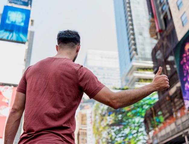 L'arrière d'un jeune homme montrant le signe ok Photo gratuit