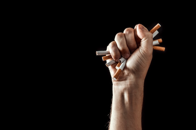 Arrière-plan créatif, une main masculine serre le poing d'une cigarette. Photo Premium