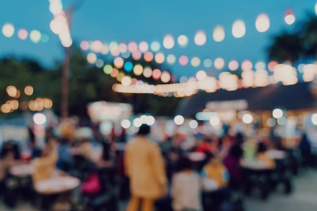 Arrière-plan flou chez les festivaliers du marché de nuit marchant sur la route. Photo Premium