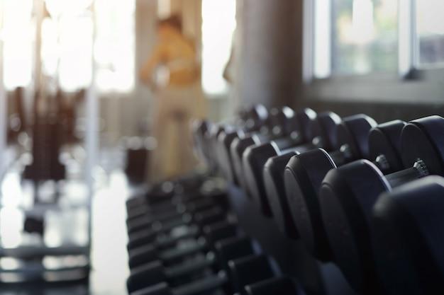 Arrière-plan flou des rangées d'haltères noirs sur une grille dans le gymnase Photo Premium