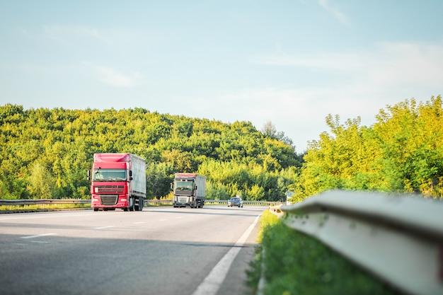 Arrivée d'un camion blanc sur la route dans un paysage rural au coucher du soleil Photo Premium