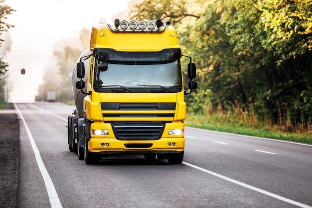 Arrivée d'un camion blanc sur la route dans un paysage rural Photo Premium