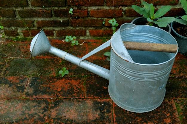 Un arrosoir galvanisé sur le sol en brique du jardin Photo Premium
