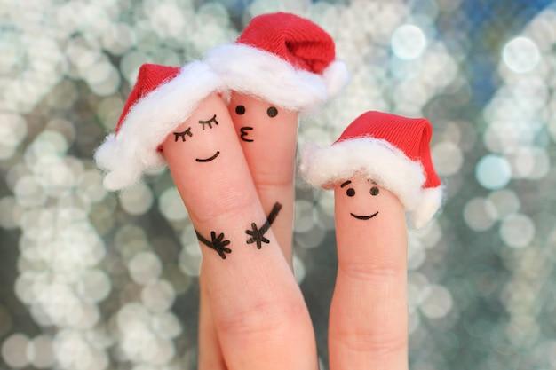 L'art des doigts de la famille fête noël. concept de groupe de personnes souriant dans les chapeaux de nouvel an. Photo Premium