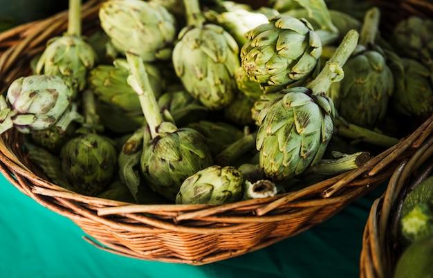 Artichauts frais en osier au marché fermier Photo gratuit
