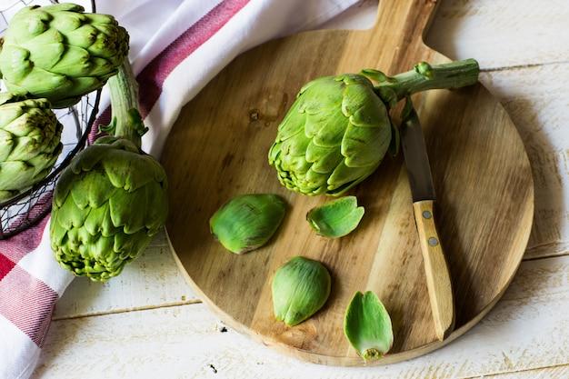 Artichauts frais pelés, préparation à la cuisson, planche à découper en bois, couteau, légumes dans un panier Photo Premium