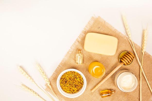 Article de spa et pollen d'abeille avec récolte de blé sur textile en jute Photo gratuit