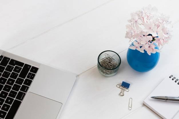 Articles de bureau et fleurs en pot sur la table Photo gratuit