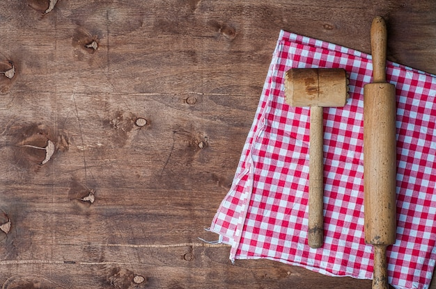 Articles de cuisine en bois sur une serviette rouge, un rouleau à pâtisserie et un marteau pour battre la viande Photo Premium