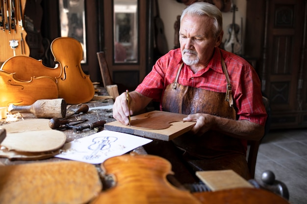 Artisan Charpentier Senior Faisant Instrument De Musique Violon Dans Son Atelier De Menuisier à L'ancienne Photo gratuit
