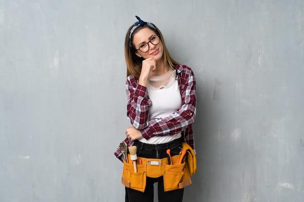 Artisan ou femme électricien avec des lunettes et souriant Photo Premium