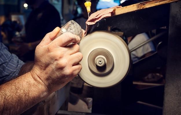 Artisan lors du ponçage d'un cendrier en cristal Photo Premium