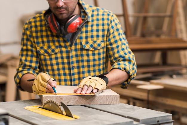 Artisan mesurant planche de bois avec règle Photo gratuit