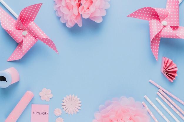 Artisanat et équipement d'art origami rose disposés dans un cadre circulaire sur fond bleu Photo gratuit
