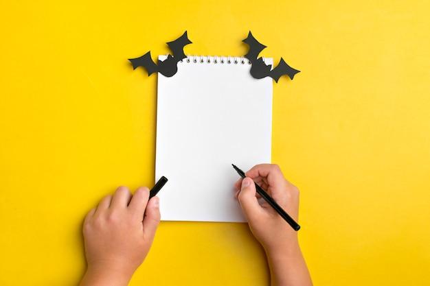 Artisanat pour les vacances de halloween. cahier blanc, bâtonnets de papier noir, l'enfant tient un stylo Photo Premium