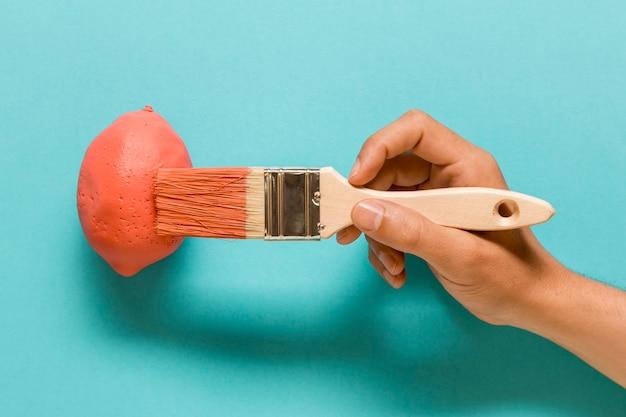 Artiste anonyme peignant un citron de couleur rose Photo gratuit