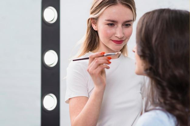 Artiste de beauté féminine se maquiller sur le modèle Photo gratuit