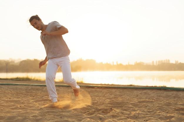 Artiste De Capoeira Athlétique Faisant Des Mouvements Sur La Plage Photo gratuit