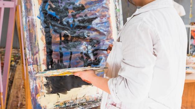 Artiste créateur peignant sur toile en utilisant un trait de peinture noire Photo gratuit