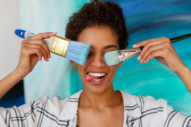 Artiste Féminine Africaine Ludique Tenant Des Pinceaux Et Faisant Des Grimaces, Montrant La Langue. Photo gratuit