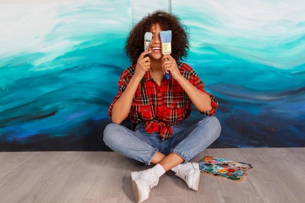 Artiste De Femme Noire Souriante En Studio Tenant Un Pinceau. étudiante Inspirée Assise Sur Ses œuvres. Photo gratuit